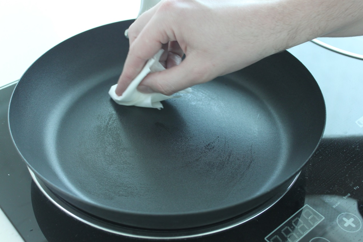 Wiping oil around a Lotus Rock frying pan