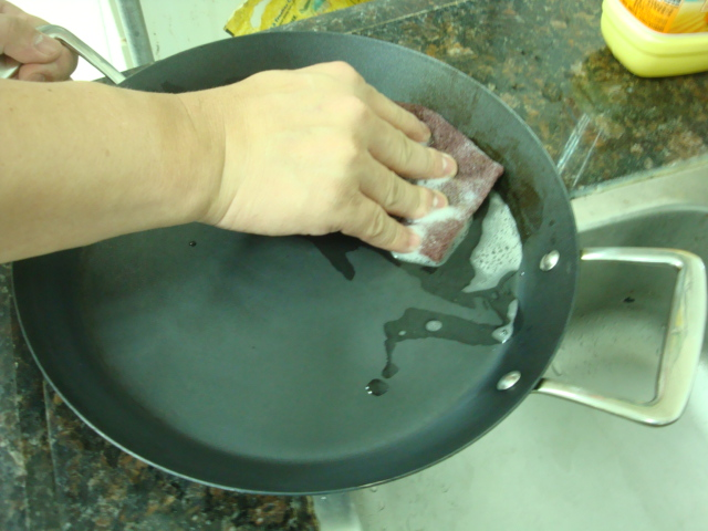 Scrubbing a pan in hot soapy water with an abrasive pad